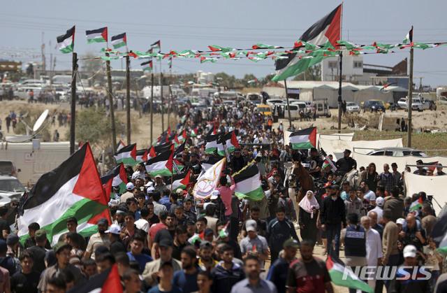 【가자시티=AP/뉴시스】15일(현지시간) 팔레스타인 시위대가 이스라엘에 땅을 빼앗긴 날로 여기는 '대재앙(나크바)의 날'을 맞아 가자지구에서 대규모 시위를 벌이고 있다. 이날 이스라엘 군이 시위대에 강경 대응하면서 약 60명의 팔레스타인인이 다쳤다. 2019.05.16