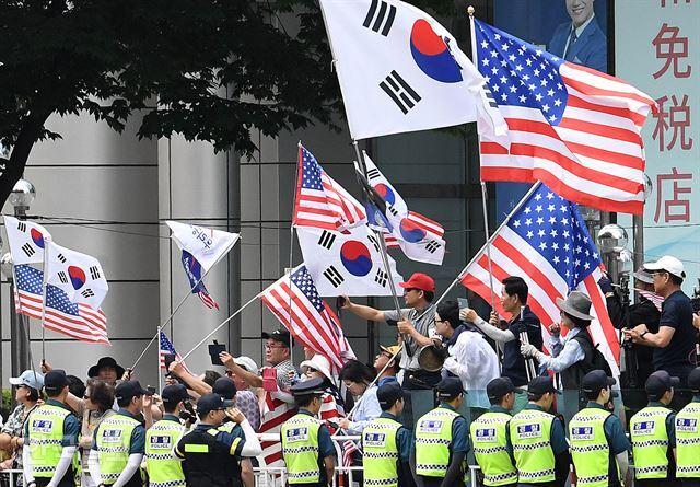 30일 서울 광화문 동화면세점 앞에 모인 우리공화당 회원들과 보수단체 회원들이 트럼프 대통령의 차량이 통과하자 성조기를 흔들며 환호하고 있다. 서재훈 기자