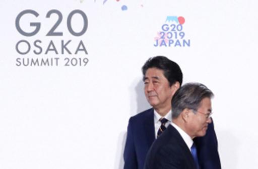 문재인 대통령(오른쪽)이 지난달 28일 오전 일본 오사카에서 열린 주요 20개국(G20) 정상회의 공식 환영식에서 의장국인 일본의 아베 신조 총리와 악수한 뒤 이동하고 있다. 오사카=연합뉴스