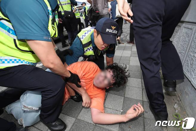22일 오후 부산 동구 일본 영사관에 대학생으로 보이는 청년 6명이 진입을 시도 했다가 경찰에 검거되고 있다. 이들은 영사관에 들어간 뒤 일본 경제보복에 항의하는 뜻으로 퍼포먼스를 하려다가 경찰에 연행됐다. 2019.7.22/뉴스1 © News1 여주연 기자