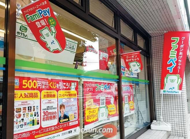 일본 도쿄 신주쿠의 패밀리마트 편의점 외부에 '파미페이(FamiPay)' 홍보물이 붙어 있다. 패밀리마트가 출시한 스마트폰 간편결제 서비스인 파미페이를 사용하는 고객에게 치킨 등 경품을 준다는 내용이다. /도쿄=최은경 특파원