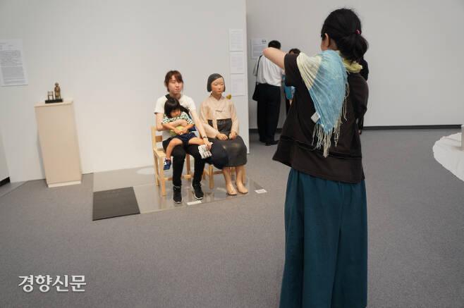 1일 일본 나고야에서 개막된 '아이치 트리엔날레 2019'의 '표현의 부자유-그후' 전시를 찾은 일본인 관람객이 '평화의 소녀상' 옆에 앉아 사진을 찍고 있다. 나고야|김진우특파원