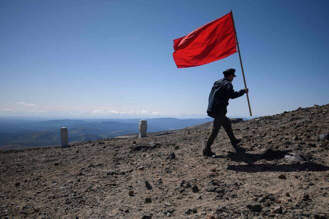 한 북한 학생이 붉은 깃발을 들고 백두산 정상으로 걸어가고 있다. [AP=연합뉴스]