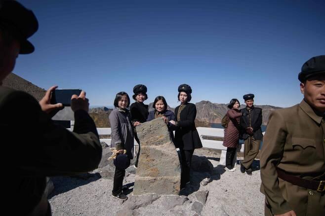 지난 11일 삼지연 백두산 정상부근 전망대에 오른 북한 학생들이 기념촬영을 하고 있다. [AFP=연합뉴스]