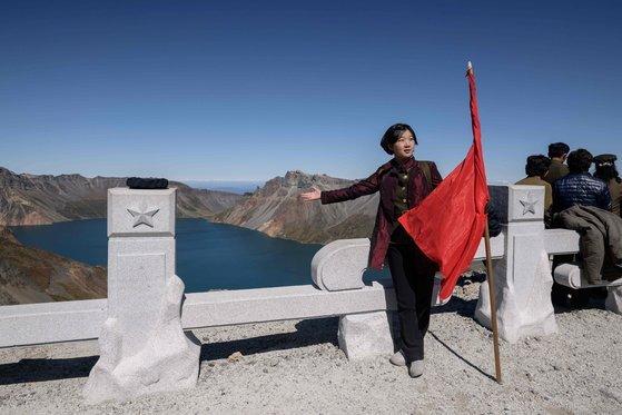 한 북한 학생이 붉은 깃발을 들고 천지를 배경으로 기념촬영하고 있다. [AFP=연합뉴스]