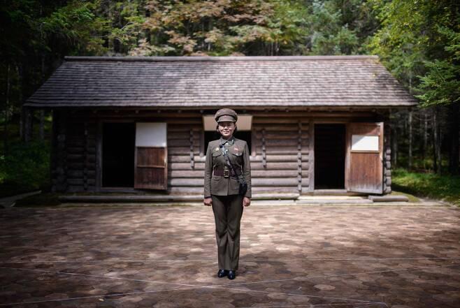 지난 12일 삼지연의 김일성 주석의 비밀 캠프이며 김정일 국방위원장이 태어났다는 오두막 앞에서 안내원 김은심(23)이 포즈를 취하고 있다. [AFP=연합뉴스]