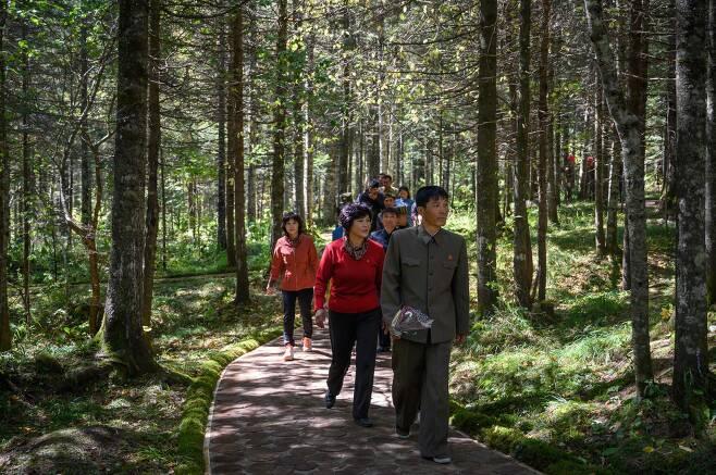 지난 12일 북한 주민들이 삼지연의 김일성 주석의 비밀 캠프를 방문하기 위해 걸어가고 있다. [AFP=연합뉴스]
