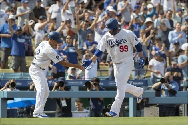 메이저리그 데뷔 후 첫 홈런을 때린 LA 다저스 류현진이 코치의 축하를 받으며 3루를 돌고 있다 (사진=연합뉴스 제공)