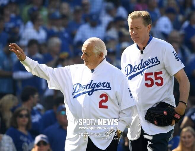 ▲ 토미 라소다 다저스 감독(왼쪽)과 오럴 허샤이저가 2018년 3월29일 미국 캘리포니아주 LA 다저스타디움에서 열린 샌프란시스코 자이언츠와 시즌 개막전에서 시구를 하기 위해 마운드에 올라가고 있다.