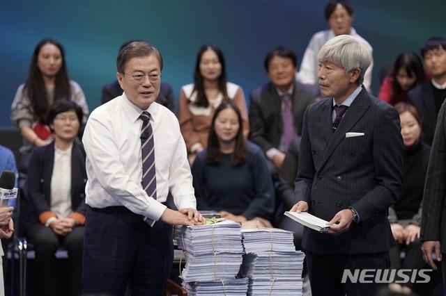 [서울=뉴시스]배훈식 기자 = 문재인 대통령이 19일 오후 서울 MBC 미디어센터에서 열린 '국민이 묻는다, 2019 국민과의 대화'에 참석해 국민패널과 온라인 참여자 질문지를 받고 있다. 2019.11.19. dahora83@newsis.com