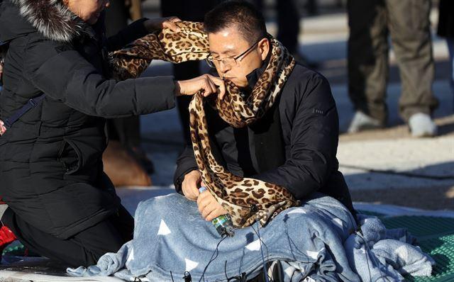 20일 오후 청와대 앞에서 한 시민이 단식투쟁을 시작한 황교안 한국당 대표에게 목도리를 둘러주고 있다. 연합뉴스.