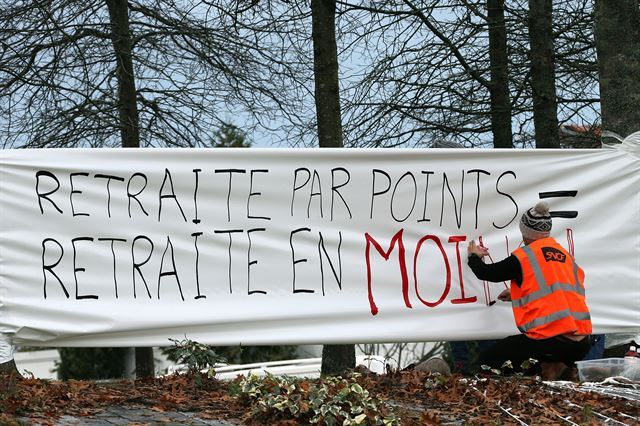 프랑스 남서부 앙글렛에서 에마뉘엘 마크롱 대통령의 연금 개혁에 반대하는 시위자가 '포인트 기반 연금=연금 축소'라는 현수막을 걸고 있다. 앙글렛=AP 연합뉴스