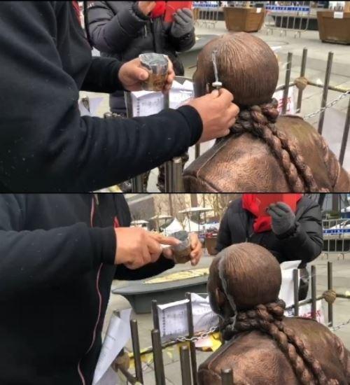 24일 머리 부분이 훼손된 전두환 동상을 접착제로 보수하고 있다. 전두환 구속 상징물 지킴이단 제공