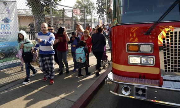 14일(현지시간) 항공유가 비처럼 내린 미국 로스엔젤레스 파크애비뉴 초등학교에서 한 학생이 소방차 옆을 지나고 있다. AP