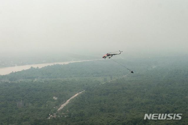 [AP/뉴스] 2019년 9월 인도네시아에서 가장 북쪽에 위치한 보르네오섬의 중앙 칼리만탄주에서 스모그 속에 헬리콥터가 산불 예방의 물 폭탄 투하 연습을 하고 있다. 보르네오섬 동 칼리만탄주로 새 수도를 옮기는 공사가 올 하반기 시작된다. 스모그는 화재 연기에서 비롯된다.  2020. 1. 17.