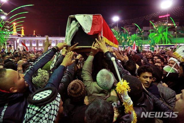 [카르발라(이라크)=AP/뉴시스]미국의 공습으로 숨진 이란 혁명수비대 쿠드스군 사령관 카셈 솔레이마니와 시아파 민병대 부사령관 아부 마흐디 알 무한디스의 장례식이 4일(현지시간) 이라크 카르발라에서 열려 지지자들이 그의 관을 옮기고 있다. 이란은 이번 미국의 공습으로 양국 간 긴장이 최고조에 달하면서 미국에 대해 '가혹한 보복'을 천명했다. 2020.01.05.