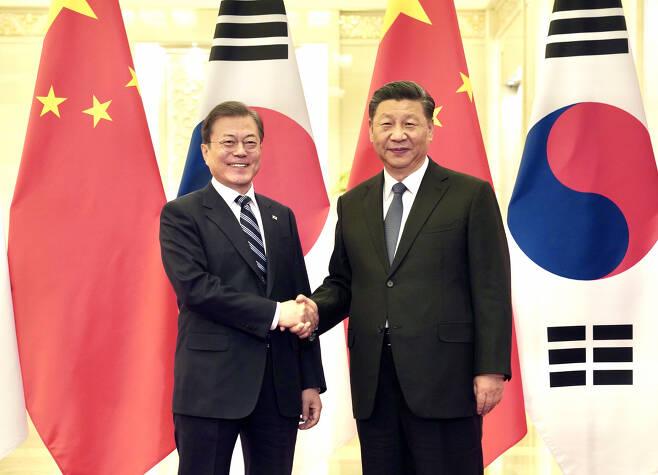 문재인 대통령과 시진핑 중국 국가주석이 지난해 12월 23일 베이징 인민대회당에서 정상회담 전 악수하고 있다. [연합]