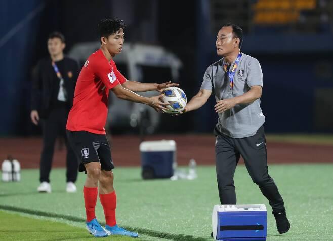 지난달 9일 태국 송클라 틴술라논 스타디움에서 열린 2020 아시아축구연맹 U-23 챔피언십 한국과 중국의 조별리그 1차전에서 김학범 감독이 정우영에게 공을 건네고 있다. [연합뉴스]