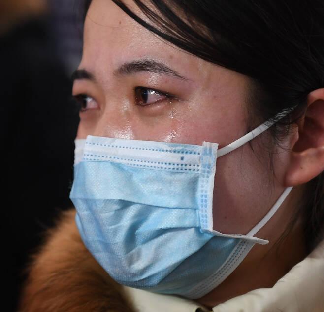 난징국제공항에서 2월11일 우한으로 향하는 의료진 남편을 배웅하는 간호사가 눈물을 흘리고 있다.