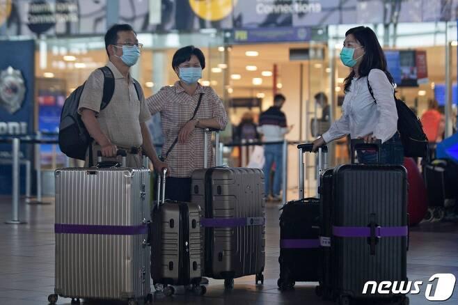 14일 칠레 산티아고의 아르투로 메리노 베니테스 국제공항에서 여행객들이 마스크를 쓴 채 대기하고 있다. © AFP=뉴스1