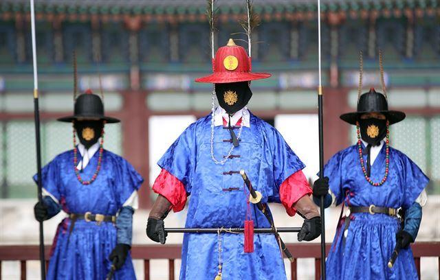 14일 오후 서울 경복궁에서 수문장들이 도깨비 문양이 들어간 마스크를 쓰고 있다. 연합뉴스