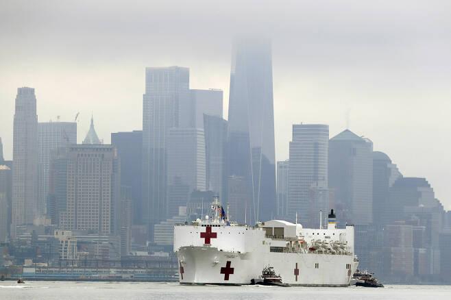 미 해군의 병원선(船) '컴포트'호(號)가 30일(현지시간) 뉴욕에 입항하기 위해 월스트리트 등이 있는 로어맨해튼 지역을 지나고 있다. 이 배엔 1000개 병상과 12개의 수술실 등이 있어 코로나19 피해로 고통받은 뉴욕을 지원할 걸로 기대된다. [AP]