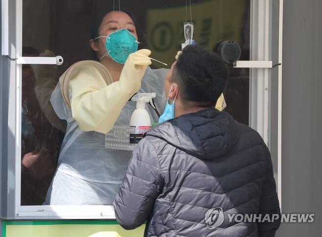 보건 당국자가 2020년 4월 3일 오후 서울 송파구 잠실종합운동장에 마련된 워크스루 방식 선별진료소에서 검체를 채취하고 있다.