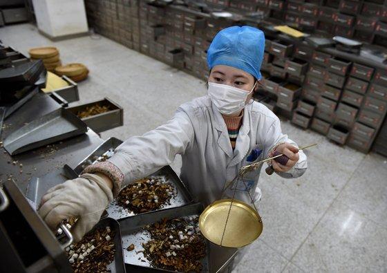지난 2월 24일 중국 안후이성의 한 대학병원에서 마스크를 낀 약제사가 한약을 조제하고 있다. 중국 정부는 중의약으로 코로나19 치료에 효과를 봤다고 주장하고 있다. [신화=연합뉴스]