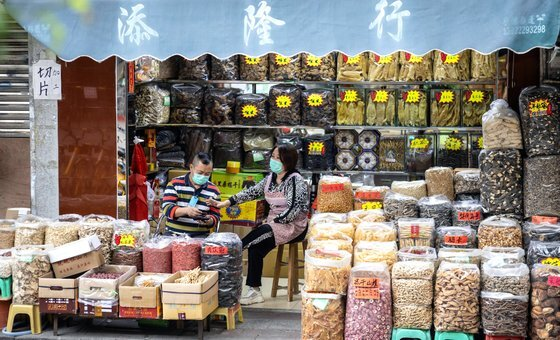 지난달 17일 중국 광둥성 광저우의 한 한약재상에 마스크를 낀 남여가 앉아 있다. 최근 중국에선 코로나19에 효험이 있다며 감기용 한약을 사재기하는 현상이 벌어지고 있다고 한다. [EPA=연합뉴스]