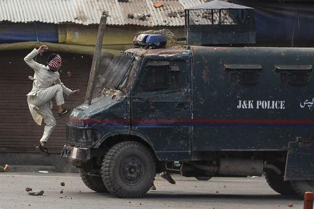 지난해 5월 복면을 한 카슈미르 시위대가 인도 경찰 차량을 공격하고 있다. 2020 퓰리처상 피쳐 사진(Feature Photography) 부문 수상작 중 한 장면. AP 연합뉴스