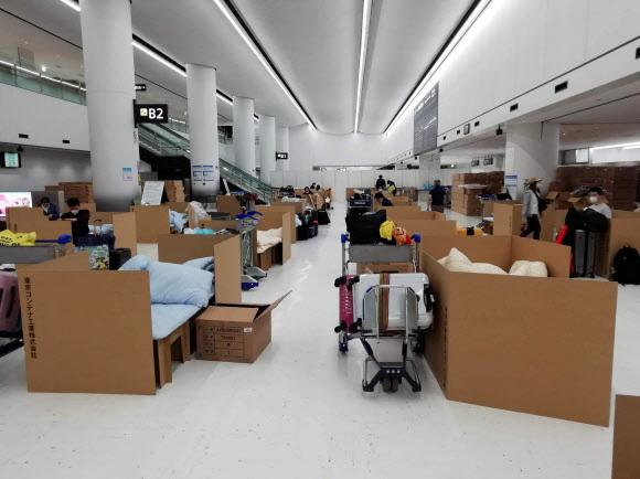 코로나 검사 결과 기다리는 日 입국자들  - 지난 8일 일본 도쿄 나리타국제공항에서 해외 입국자들이 골판지 박스로 칸막이를 한 임시 침대에서 코로나19 검사 결과를 기다리고 있다. 일본 정부는 미국과 중국, 이탈리아 등 해외 입국자들을 대상으로 코로나19 검사를 실시하고 있다.도쿄 AP 연합뉴스