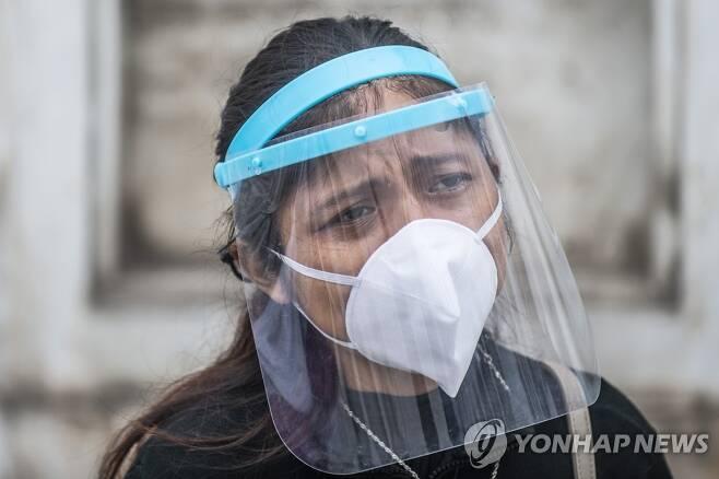 마스크와 얼굴 가리개를 착용하고 친지 장례식에 참석한 페루 여성 [AFP=연합뉴스]