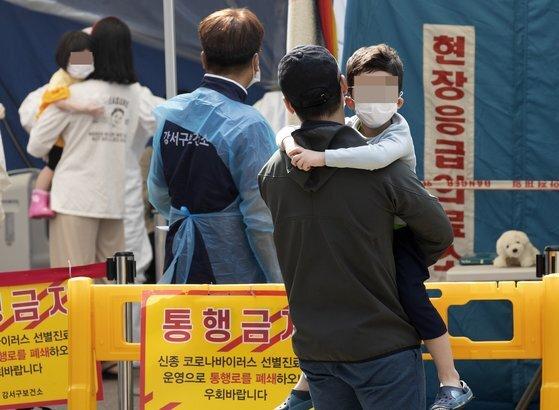 지난 26일 오전 부모님과 함께 서울 강서구 보건소 선별진료소를 찾은 어린이들이 신종 코로나바이러스 감염증(코로나19) 검사를 받은 후 진료소를 나서고 있다. 연합뉴스