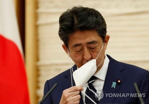 (도쿄 AFP=연합뉴스) 아베 신조(安倍晋三) 일본 총리가 25일 일본 총리관저에서 열린 기자회견에서 발언에 앞서 마스크를 벗고 있다. 2020.5.31