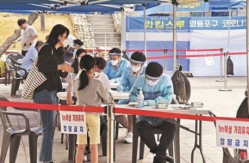 시민들이 31일 서울 영등포구 자매근린공원에 마련된 코로나19 워크스루 선별진료소에서 검사를 받고 있다. 이 지역 건물에 위치한 한 학원에서는 강사와 학생들의 가족을 포함해 9명이 코로나19 확진 판정을 받았다. 김지훈 기자