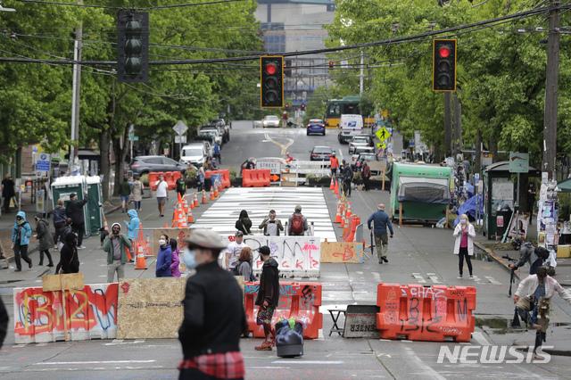 [시애틀=AP/뉴시스]11일(현지시간) 워싱턴 시애틀에서 행인들이 칼 앤더슨 공원 인근 도로에 설치된 바리케이드를 지나고 있다. 2020.06.12.