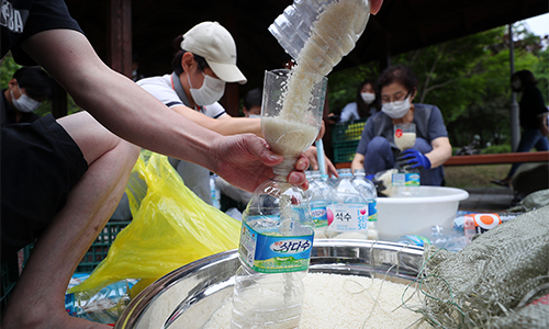 탈북단체 '큰샘' 회원들이 지난 18일 서울 강남구 일원동 일대에서 북한에 보낼 쌀을 페트병에 담고 있다. 뉴시스