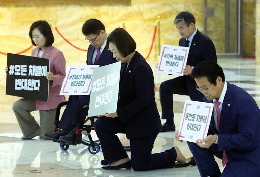 미래통합당 의원들이 지난 10일 국회 중앙홀에서 미국 흑인 조지 플로이드 사태와 관련, '모든 차별에 반대한다'는 팻말을 들고 한쪽 무릎을 꿇은 채 시위를 하고 있다./연합뉴스
