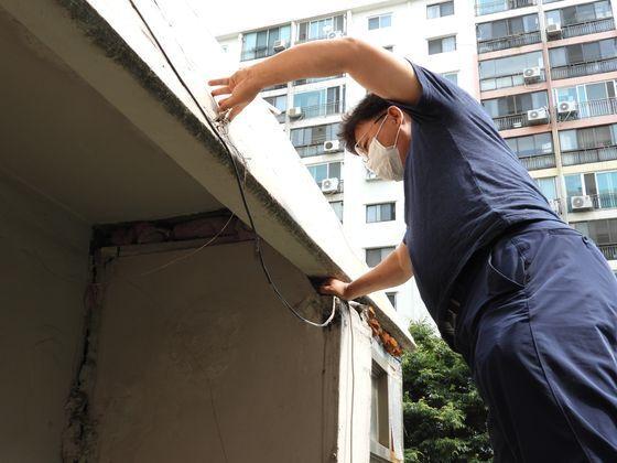 인천 삼두1차 아파트의 경비실이 지반침하로 주저앉아 지붕과 벽체 사이에 어른 주먹이 들어갈 정도로 틈이 벌어졌다. 주민대표인 조기운씨가 직접 손을 넣어 보이고 있다. 강찬수 기자.