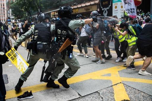 지난 1일 보안법 반대 시위를 진압하던 한 홍콩 경찰(왼쪽)이 취재기자들(오른쪽)을 향해 최루액을 뿌리고 있다. 홍콩 경찰은 '홍콩독립' 깃발을 소지한 한 시위 참가자가 첫 보안법 위배 사범으로 체포됐다고 밝혔다. 홍콩=AFP연합뉴스