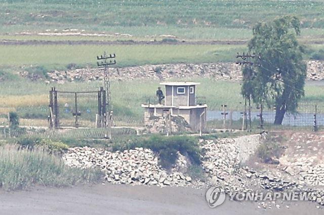 지난달 9일 북한 황해북도 개풍군 마을 철책을 지키는 북한 병사가 몸을 푸는 듯 한 발로 서있다. 연합뉴스