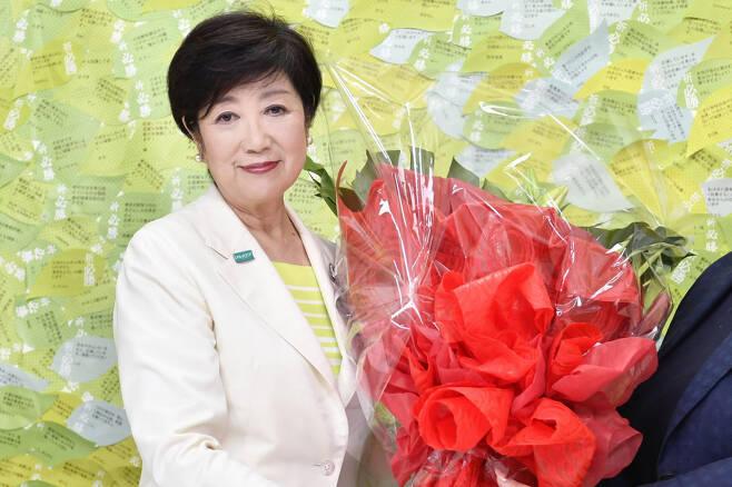 고이케 유리코(小池百合子·67) 도쿄도지사가 당선이 확정된 후 축하 꽃다발을 들고 있는 모습. [AP]
