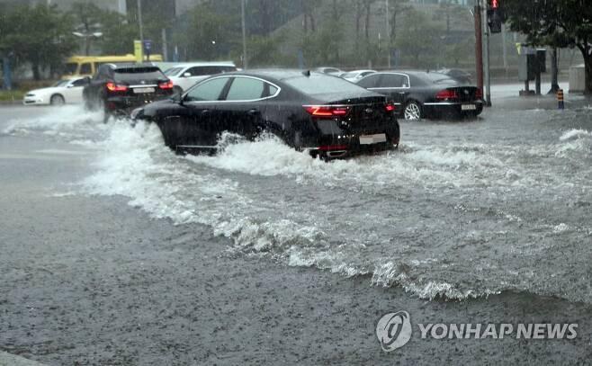 집중호우 해운대 도로 물바다 (부산=연합뉴스) 조정호 기자 = 10일 호우경보가 내려진 부산 해운대구 센텀시티에서 차량들이 도로 침수 구간을 물보라를 일으키며 겨우 지나가고 있다. 2020.7.10 ccho@yna.co.kr