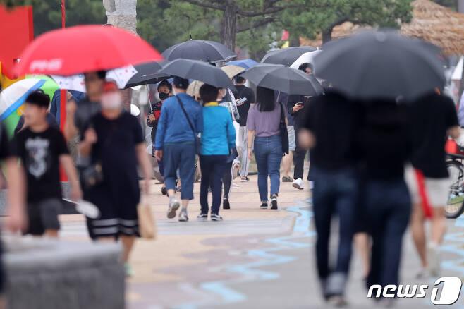 경북 포항시 북구 영일대해수욕장을 찾은 시민들과 관광객들이 우산을 받쳐들고 해안길을 걸어가고 있다. 2020.7.12/뉴스1 © News1 최창호 기자