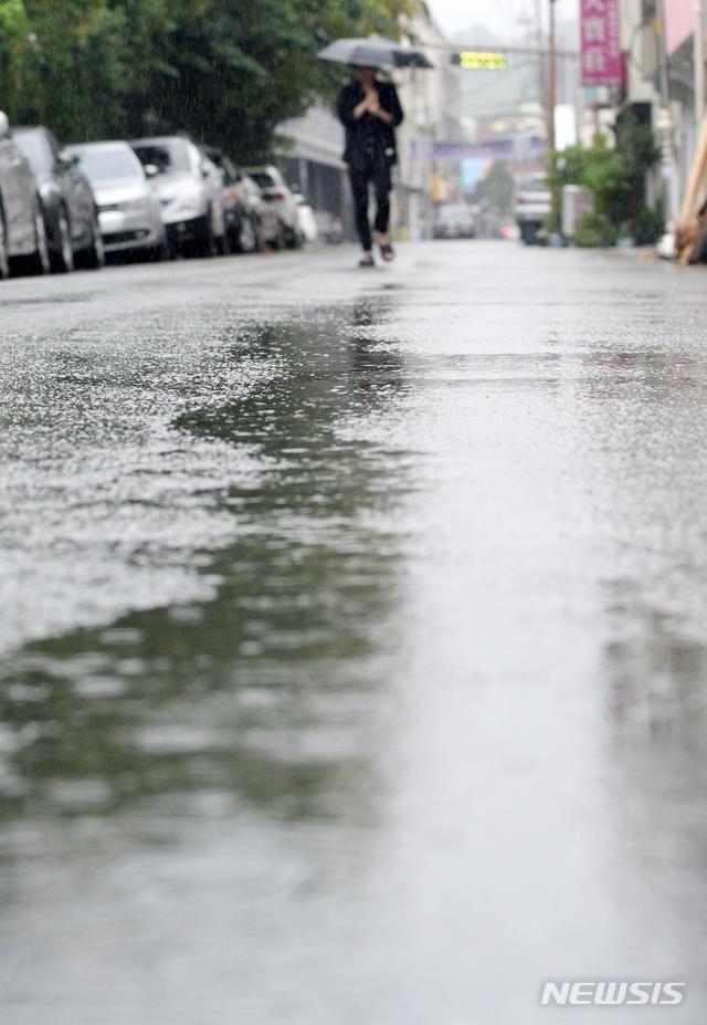 [전주=뉴시스] 김얼 기자 = 전국적으로 장맛비가 쏟아져 내린 6일 전북 전주시 전라감영 일원에서 한 시민이 우산으로 비를 피하며 길을 지나고 있다. 2020.07.06.pmkeul@newsis.com