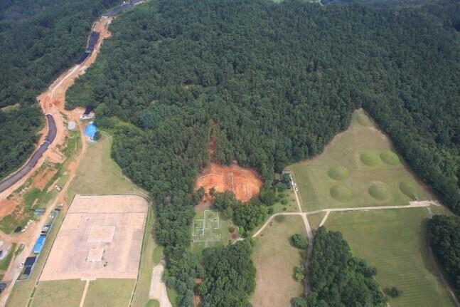 하늘에서 본 능산리 고분군. 아래쪽으로 돌출된 숲 한가운데 누런 땅 드러난 부분이 서고분군의 8, 10호분 발굴지점이다. 숲 오른쪽의 잔디밭 봉분들이 사적 지정된 기존 능산리 고분군이다. 숲 왼쪽의 허옇고 큰 건물터는 1993년 금동대향로가 나온 능사 터다. 사진 한국전통문화대 고고학연구소 제공