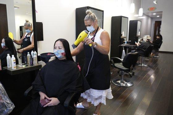 지난 5월 미국 캘리포니아주 로즈빌에 있는 미용실에서 미용사와 손님 모두 마스크를 쓰고 있다. [AP=연합뉴스]