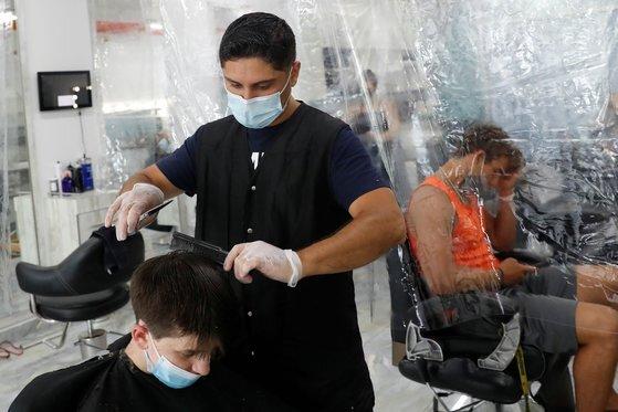 지난달 미국 뉴욕 미용실에서 미용사와 손님 모두 마스크를 착용한채 머리를 손질하고 있다. [로이터=연합뉴스]