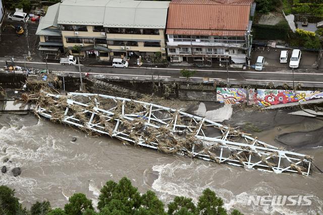 [히타=AP/뉴시스] 일본 오이타현 히타에 지난 8일 기록적인 폭우로 불어난 강물에 끊긴 다리 구조물이 쓰러져 있다. 2020.07.09