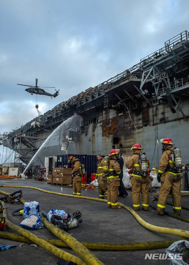[샌디에이고= AP/뉴시스] 미국 샌디에이고 해군기지에서 화재가 난 USS본홈 리처드 해군함정에서 15일 진화작업에 나선 소방대원들과 소방용 헬기.